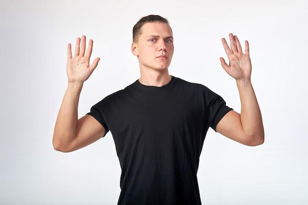 Bange man met een zwart katoenen t-shirt met korte mouwen steekt zijn hand op.