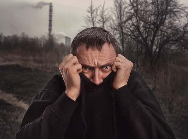 Bange man verbergt zijn gezicht in trui op de natuur