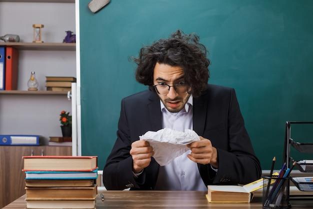 Bange mannelijke leraar met een bril die vasthoudt en kijkt naar verpletterend papier dat aan tafel zit met schoolgereedschap in de klas
