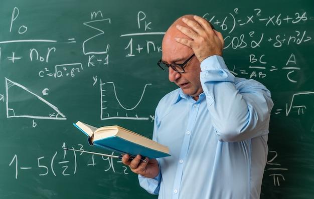 Bange mannelijke leraar van middelbare leeftijd met een bril die voor het schoolbord staat en een boek met de hand op het hoofd zet
