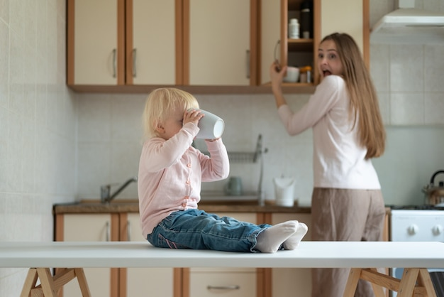 Bange moeder en klein kind met mok in hun handen in de keuken. kind zonder toezicht.
