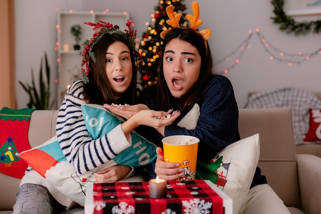 Bange mooie jonge meisjes met hulstkrans en rendierhoofdband houden popcorn vast en kijken tv zittend op fauteuils kersttijd thuis