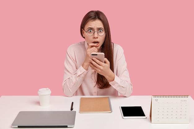 Bange ontevreden vrouw houdt mobiele telefoon vast, heeft alles netjes op tafel gerangschikt
