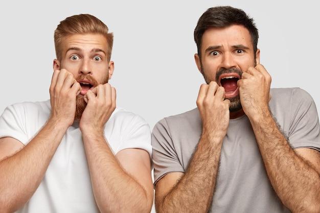 Bange, onzekere mannenvrienden kijken naar de camera met bezorgde, angstige uitdrukkingen