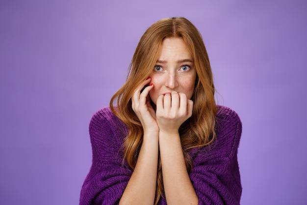 Bange onzekere vrouw met rood haar die vingernagels bijt en zich bang voelt als alleen thuis en rare gruwelijke geluiden hoort trillen van angst die angstig en bezorgd over paarse achtergrond staat.