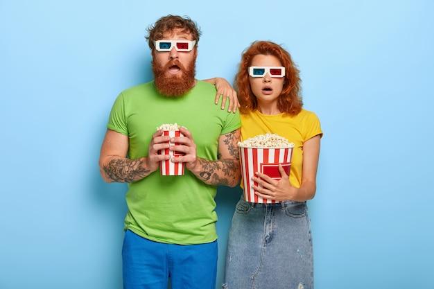 Bange roodharige vrouw en man die diep onder de indruk zijn van film