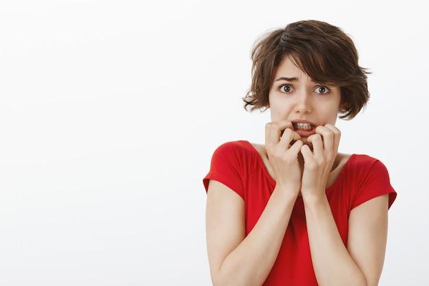 Bange timide vrouw die huivert van angst, bang kijkt