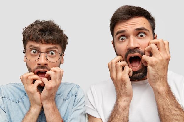 Bange twee mannen hebben angstige uitdrukkingen, kijken zenuwachtig, merken een vreselijk ongeluk op de weg op, reageren op iets vreselijks