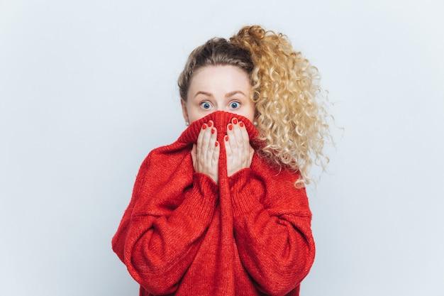 Bange verbijsterde vrouw ziet haar fobie, bedekt gezicht met kraag van rode trui