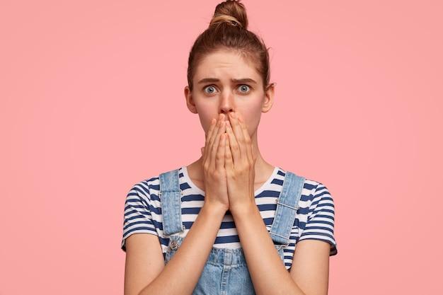 Bange vrouw bedekt mond met beide handen, kijkt met een bange uitdrukking, ontvangt slecht nieuws