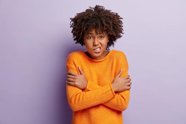 Bange vrouw beeft van angst, kruist handen over de borst, voelt ijskoud, klemt haar tanden op elkaar, draagt een oranje casual trui, geïsoleerd over paarse muur, fronst gezicht. ongelukkig meisje voelt zich koud binnen