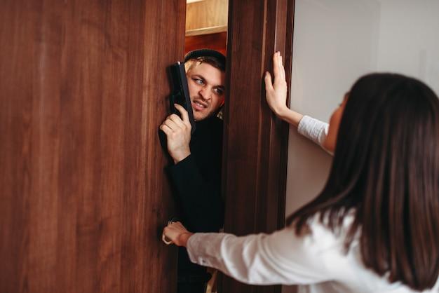 Bange vrouw die de deur probeert te sluiten, moordenaar in zwarte kleding met pistool in handen wil het appartement binnendringen. overval thuis
