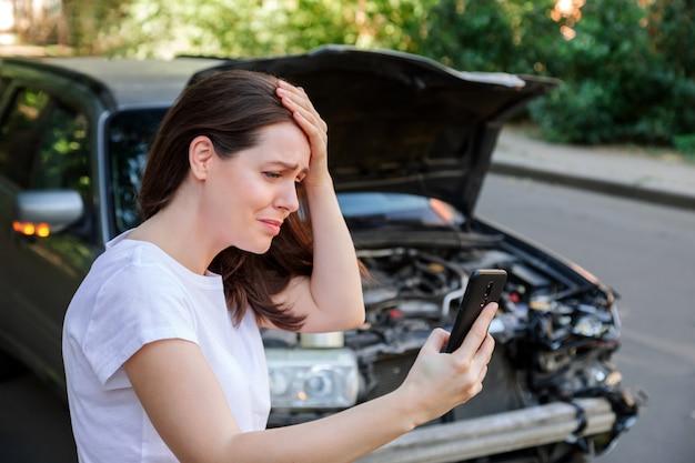Bange vrouw in stress die haar hoofd vasthoudt na een auto-ongeluk dat de autoverzekering om hulp roept. bestuurder vrouw voor vernielde auto in auto-ongeluk. gevaarlijke verkeerssituatie.