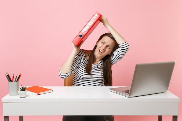 Bange vrouw verdedigt zich achter rode map met papieren document dat aan project werkt terwijl ze op kantoor zit met laptop geïsoleerd op pastelroze achtergrond. prestatie zakelijke carrière concept. kopieer spa
