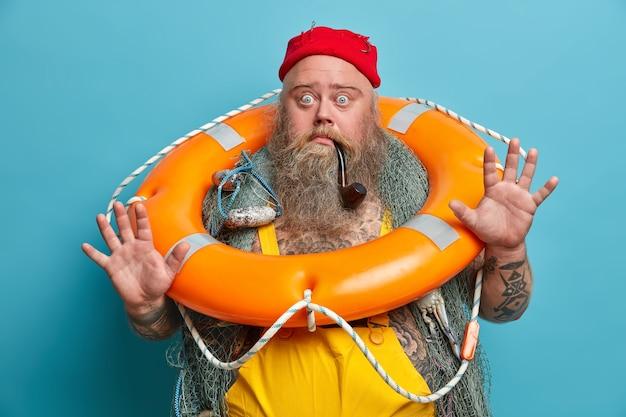 Bange zeeman heft palm op, staart afgeluisterde ogen, schrikt van smimming, poseert met oranje opgeblazen reddingsboei, visnet, zeeziek zijn