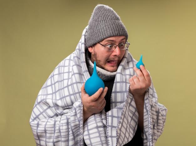 Bange zieke man van middelbare leeftijd die een wintermuts en sjaal draagt, gewikkeld in een plaid die vasthoudt en naar klysma's kijkt