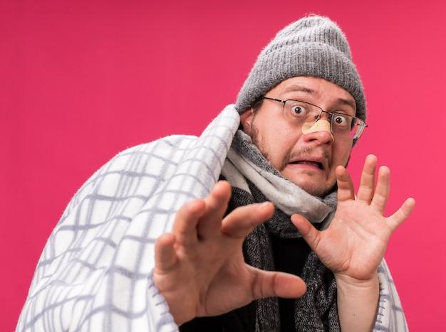 Bange zieke man van middelbare leeftijd met een wintermuts en een sjaal gewikkeld in een plaid die zijn handen naar de camera steekt