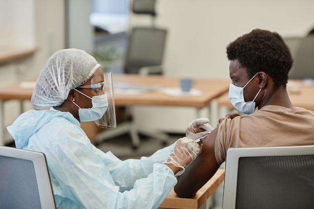 Bange zwarte jongeman die ogen sluit wanneer hij een vaccin tegen het coronavirus krijgt