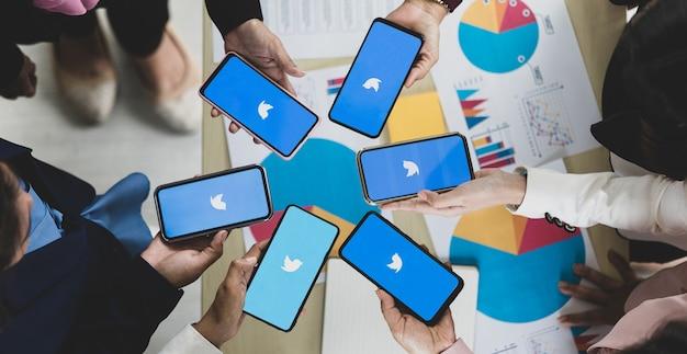 Bangkok/thailand - 06 augustus 2021: mensen hebben smartphones in verschillende merken en verschillende besturingssystemen met logo's van sociale twitter-toepassingen.
