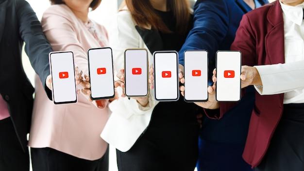 Bangkok/thailand - 06 augustus 2021: mensen houden smartphones in verschillende merken en verschillende besturingssystemen met logo's youtube, het populairste videoportaal ter wereld.