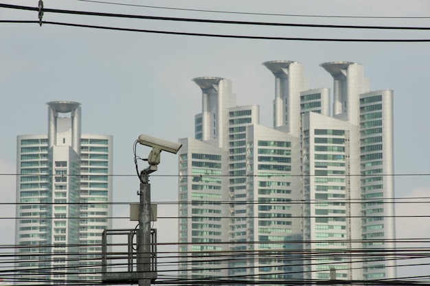 Bangkok, thailand - 12 december 2010: bewakingscamera in de straten van bangkok, en moderne gebouwen op de achtergrond