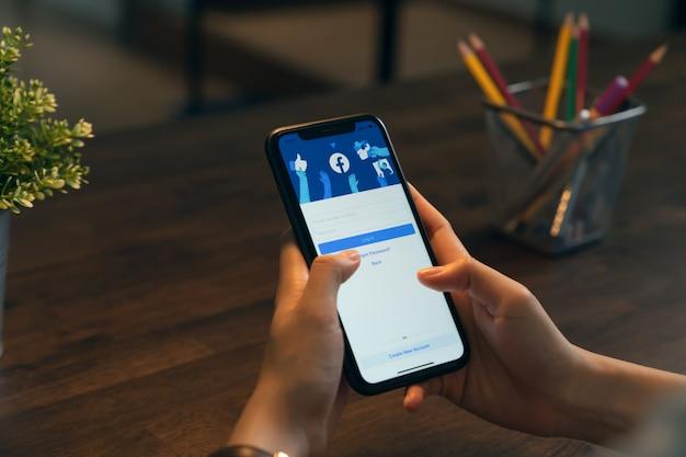 Bangkok, thailand - 13 april 2020: hand houdt telefoon en het facebook-scherm op apple iphone vast, sociale media gebruiken voor het delen van informatie en netwerken.