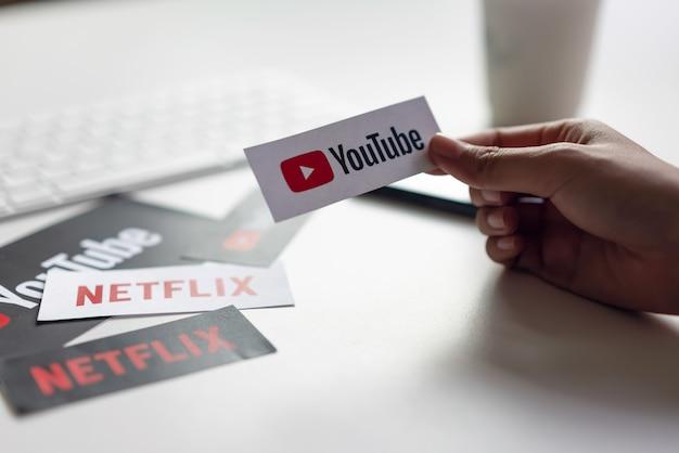Bangkok, thailand - 18 maart 2019: hand drukt op scherm toont de youtube app-pictogrammen op papieren etiket.
