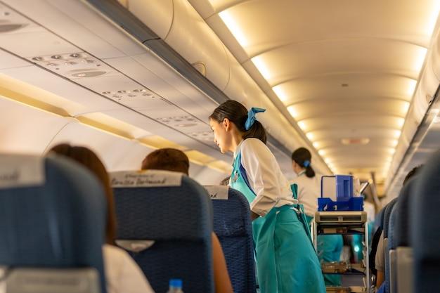 Bangkok, thailand - 27 september, 2018 - bangkok airways-stewardess dient drank aan passeng