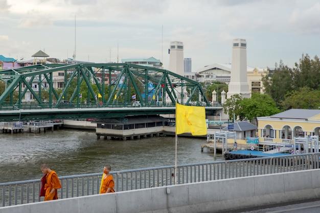 Bangkok / thailand - 7 juli 2020: monnik loopt op de brug uitzicht vanaf chao phraya sky park, chao phraya-rivier dichtbij phra pokklao-brug in, thonburi, bangkok, thailand.