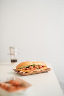 Banh mi xiu mai - vietnamees broodje met gehaktballetjes in tomatensaus, do chua (radijs en wortel augurk), komkommer en koriander.
