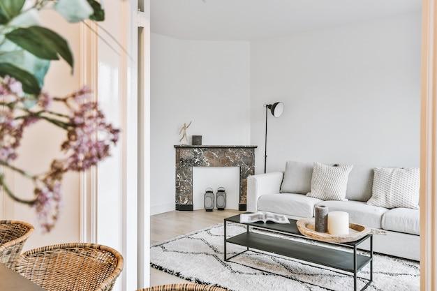 Bank en tafel met decoraties geplaatst in de buurt van marmeren open haard achter deuropening van eetkamer in elegant appartement
