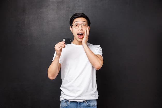 Bank, financiën en betalingsconcept. portret van opgewonden en geamuseerde aziatische man in t-shirt, open mond gefascineerd praten over creditcardkenmerken, staande zwarte muur geïntrigeerd
