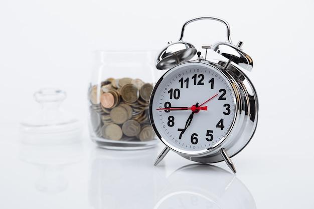 Bank met muntstukken en wekkerclose-up. tijd is geld concept