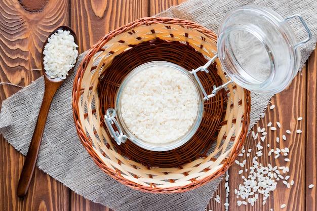 Bank met rijst en houten lepel in een mand
