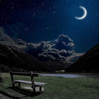 Bank om te ontspannen met uitzicht op de nachtelijke alpen in oostenrijk. elementen van deze afbeelding geleverd door nasa