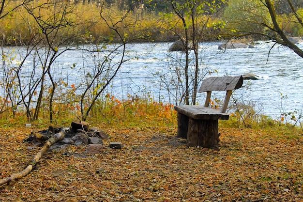 Bank op de rivieroever in de herfst