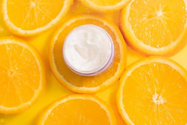 Bank van witte vochtinbrengende dikke crème voor gezicht en lichaam op een achtergrond van sinaasappelen. natuurlijk vitamine c-product voor anti-verouderingseffect.
