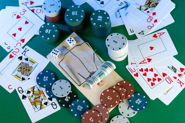 Bankbiljet en muizenval, spelval, tegen de achtergrond van casinofiches en dobbelstenen.