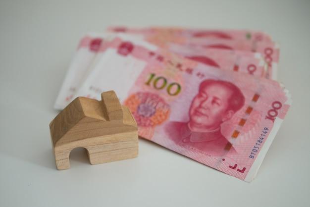 Bankbiljet valuta chinese yuan en houten huis blok voor onroerend goed en grond bedrijfsconcept
