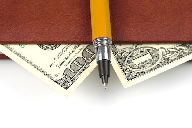 Bankbiljetten en een rode pen die in het notitieboekje liggen. financiën en onderwijs