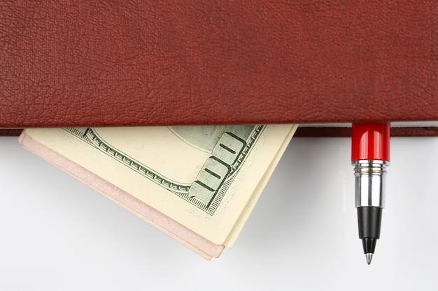 Bankbiljetten en een rode pen die in het notitieboekje liggen
