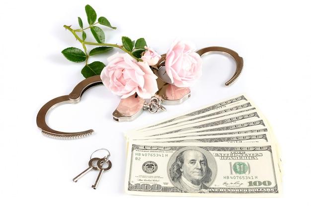 Bankbiljetten en handboeien met roze bloemen en sleutels
