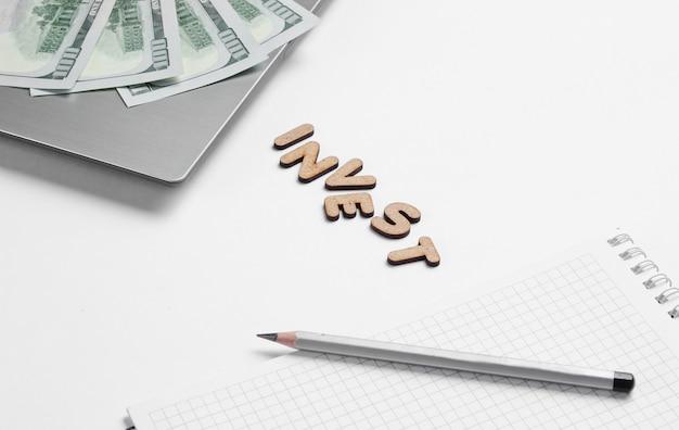 Bankbiljetten op een laptop en een leeg notitieboekje