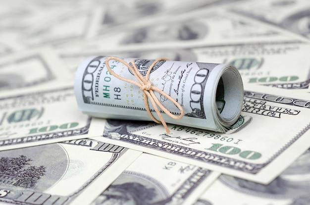 Bankbiljetten opgerold en vastgezet met band liggend op veel bankbiljetten
