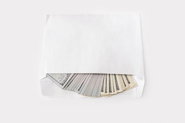 Bankbiljetten van 100 dollar in een witte envelop op een witte achtergrond