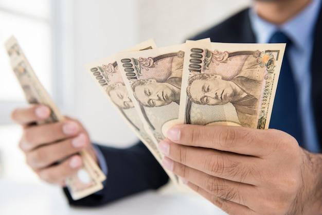 Bankbiljetten van de zakenman de tellende geld japanse yen