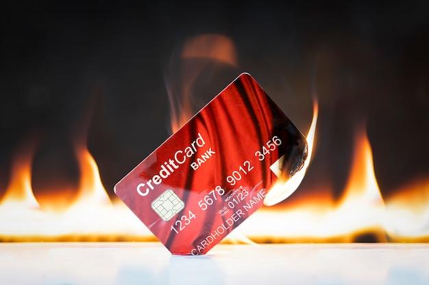 Bankcreditcard in vlammen op zwarte achtergrond. concepten van de ineenstorting van de financiële markten en het krediet- en financiële systeem. sancties en loskoppeling van het snelle systeem.