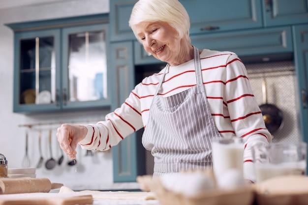 Banketbakker. aangename vrolijke oudere vrouw in een schort die deeg maakt in de keuken en het met wat bloem bestrooit