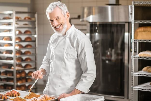 Banketbakker, bakkerij. vrolijke volwassen grijsharige man in uniform met kwastje in de buurt van dienblad met vers gebakken croissants in bakkerij
