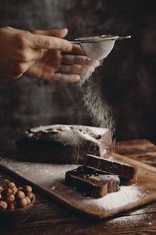 Banketbakker bestrooit chocoladebrownie in poedervorm met poedersuiker